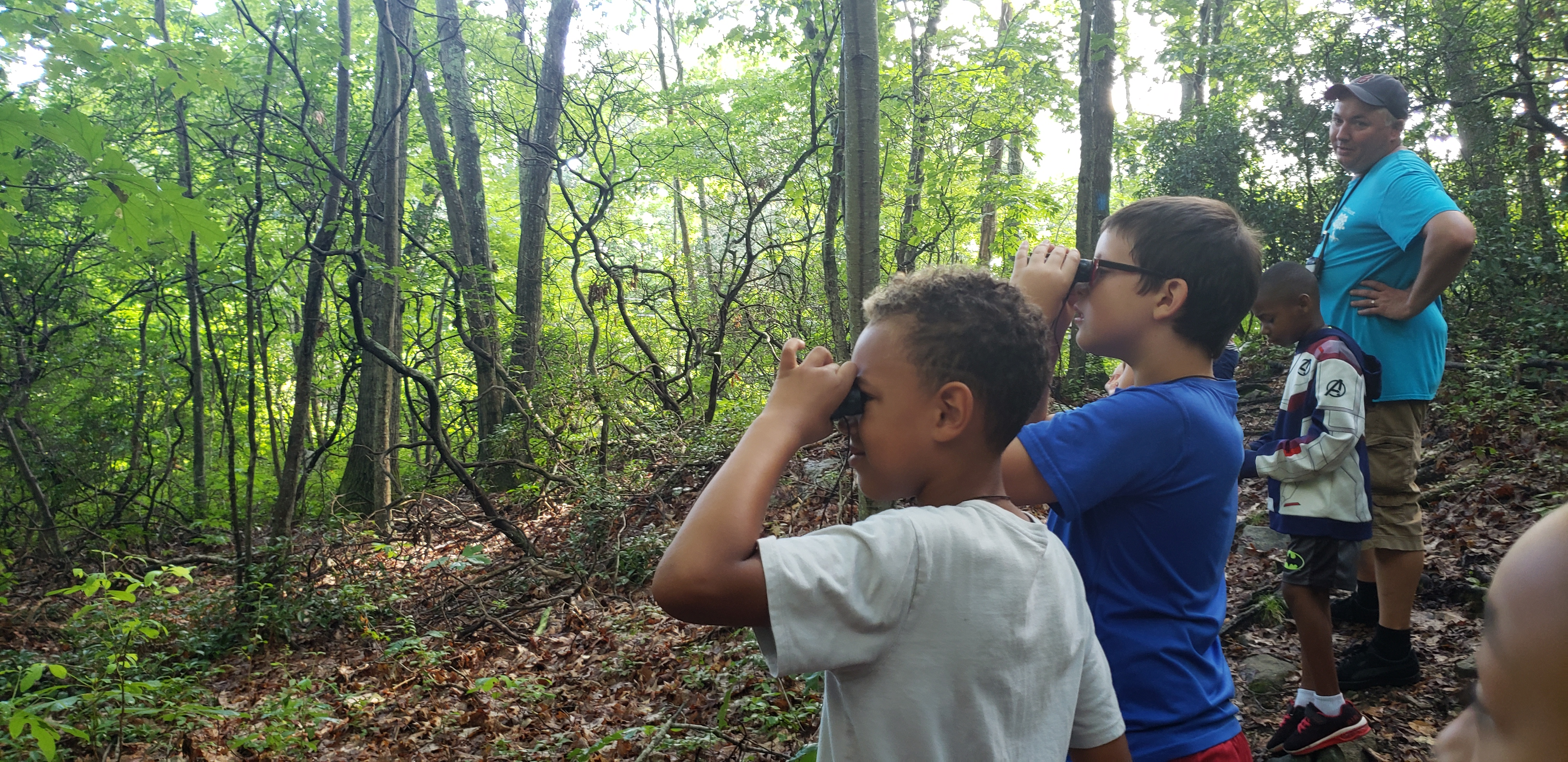 Two Tree House students standing on trail holding binoculars